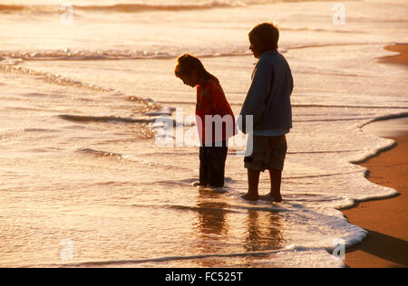 Boy and girl standing in shallow shore waves at sunset - Stock Image