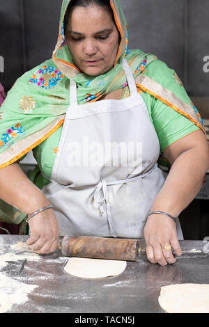 A middle aged Sikh woman in traditional ethnic clothing volunteers and prepares roti  to be served in the temple's langar (dining hall). In Queens,NY - Stock Image
