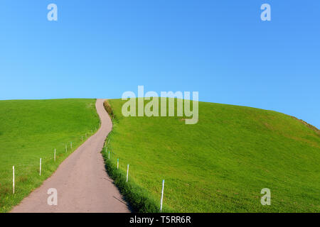 rural road on hill with blue sky - Stock Image