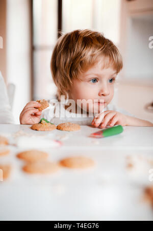 A small happy toddler boy sitting at the table, decorating and eating cakes at home. - Stock Image