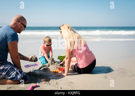 Family of 3 playing in the sand on the beach, Riviera Nayarit, Mexico - Stock Image