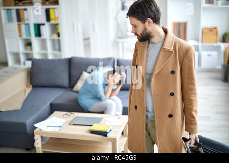 Young man in beige coat pulling suitcase while leaving for business travel on background of lonely woman - Stock Image