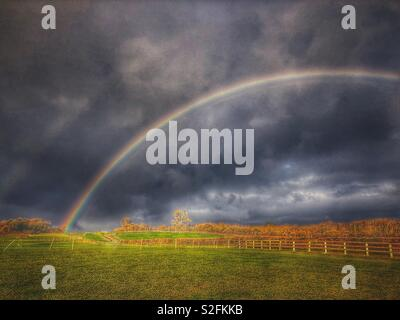 Double rainbow and dramatic storm clouds over rural landscape - Stock Image