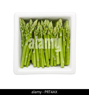 Pieces of asparagus in a square bowl isolated on white background; - Stock Image