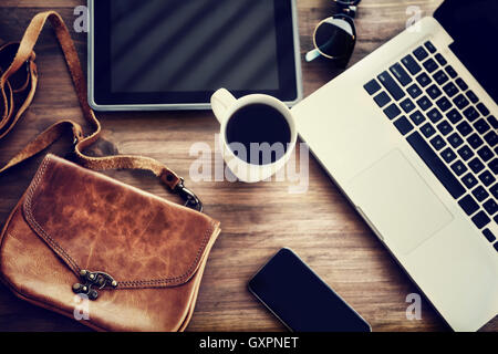 Working place: laptop, tablet, phone, cup of coffee and stylish bag on the table of a business woman, lifestyle - Stock Image