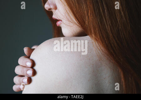 young woman with red hair and freckles on bare shoulder - skin or body care concept - Stock Image