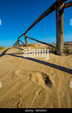 Human foot mark on sand beach next to a barrier - Stock Image