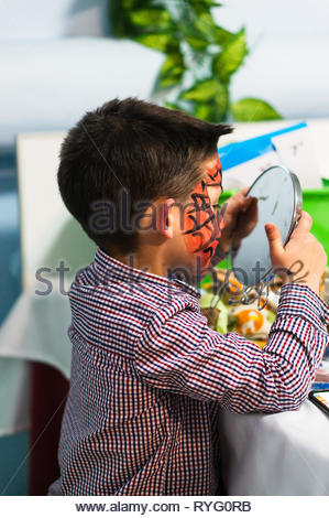 Poznan, Poland - March 2, 2019: Young boy with red face paint looking in a mirror by a table during a birthday celebration party. - Stock Image
