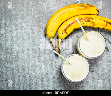 Banana smoothie with milk. On rustic background. - Stock Image