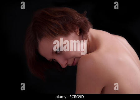 Young sensual woman beauty portrait against dark background - Stock Image