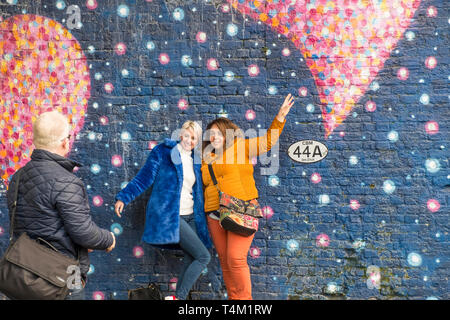Friends posing for a photograph against a large colourful mural painted on a wall in London. - Stock Image