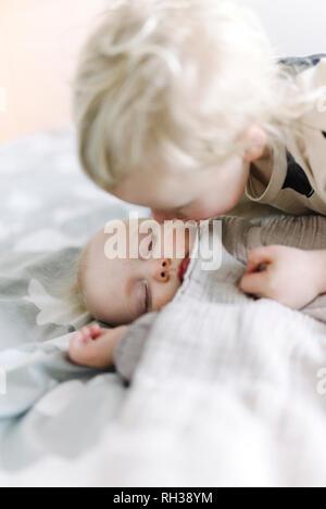 Sister kissing sleeping brother - Stock Image