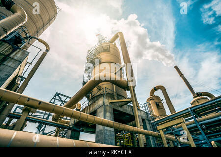 Looking up towards the sky surrounded by the tanks and tubes of a geothermal power plant releasing steam in Calipatria in California. - Stock Image