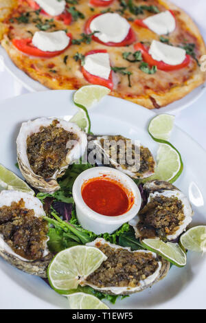 Miami Beach Florida Ocean Drive food restaurant plate oysters lime wedges pizza Caprese display - Stock Image