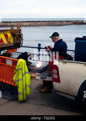 A welder repairing corroded hand rails on the sea wall Staithes North Yorkshire in preparation for the coming busy tourist season - Stock Image