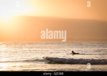 Man surfing at Byron Beach in Byron Bay. - Stock Image