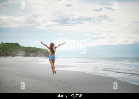 Attractive woman raising arms happily walking at a beach - Stock Image
