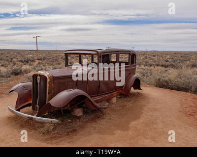 1932 Studebaker at Route 66 exhibit, Petrified Forest National Park, Arizona. Route 66 followed the telephone line in the background - Stock Image