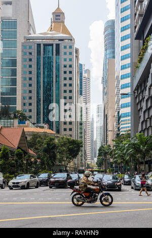 A motorcyclist on Cross Street passes the junction with Robinson Road, Singapore - Stock Image