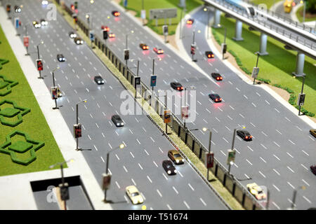 Model of city street with multi lane highway with traffic travelling in both directions and flyover to the right - Stock Image