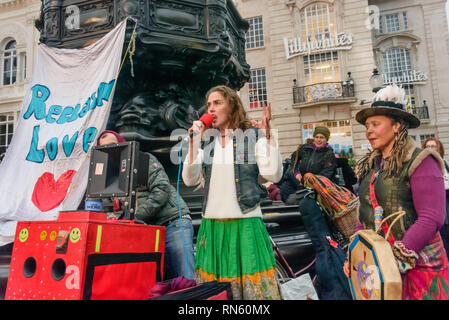 London, UK. 16 February 2019. Venus CuMara speaks with Alex Akal, at right. The 16th 'Reclaim Love' free Valentine's Day street party takes place around the statue of Eros in Piccadilly Circus, with drumming, music, dancing poetry to celebrate love. The event, which was founded by poet Venus CuMara, aims to reclaim love as a manifestation of the human spirit from the sleazy commercialisation which has taken over Valentine's Day as a festival of profit. Credit: Peter Marshall/Alamy Live News - Stock Image