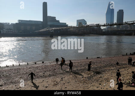 View of River Thames at low tide Tate Modern Art Gallery building & British primary schoolchildren mudlarking London UK Great Britain  KATHY DEWITT - Stock Image