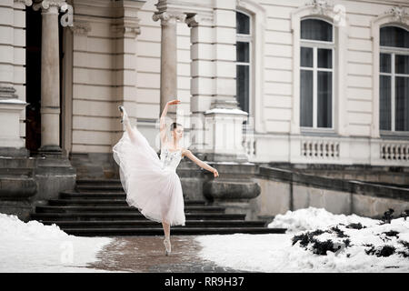 Beautiful ballerina dancing in white dress next to building on snow background. Arabesque ballet pose. - Stock Image