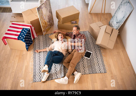 overhead view of happy couple laying on floor surrounded by cardboard boxes - Stock Image