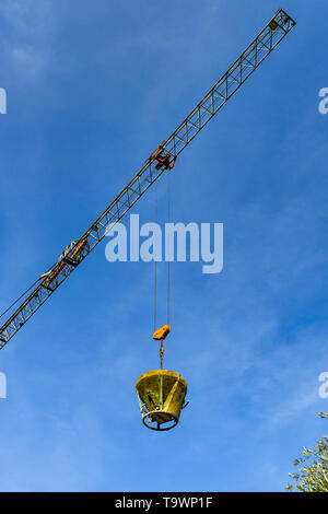 GARDA, LAKE GARDA, ITALY - SEPTEMBER 2018: Tower crane lowering a heavy steel bucket of concrete on a building site in the town of Garda on Lake Garda - Stock Image