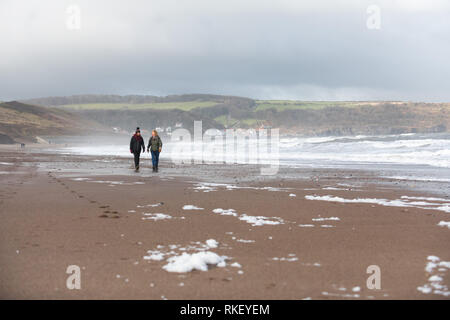 Whitby, Yorkshire, UK. 11th February, 2019. U.K. Weather. Whitby, North Yorkshire, England. 11th February 2019. Visitors to the North Yorkshire coast at Whitby enjoying a bright but cold walk and taking in the fresh sea air along the seashore. Alan Beastall/ /Alamy Live News - Stock Image