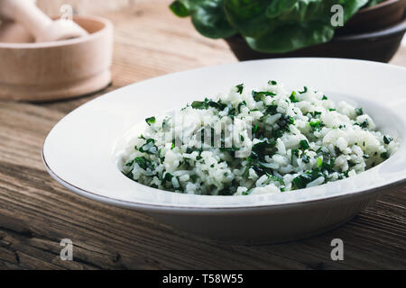 Spinach rice served in white plate on rustic wooden table with fresh green leaf vegetables, plant based meal, close up, selective focus - Stock Image