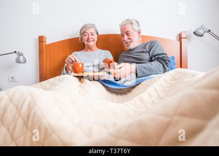 Old senior mature caucasian couple enjoy breakfast in the morning at bed in the bedroom at home - retired people live together and eat healthy food to - Stock Image