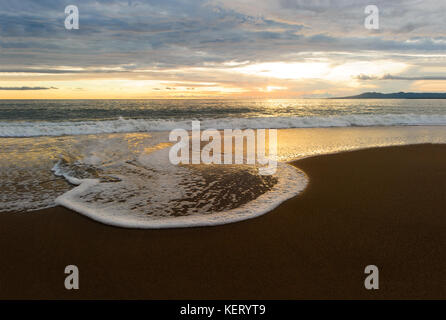 Sunset ocean is a serene scenic seascape on the beach with the bright sun setting on the ocean horizon as a gentle - Stock Image