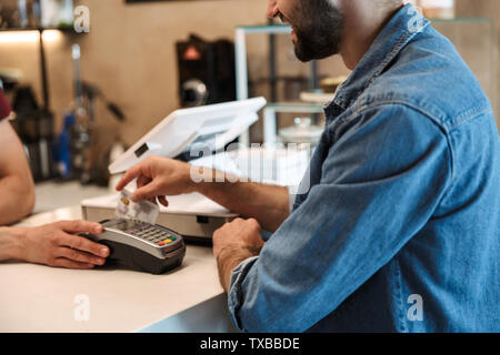 Photo of smiling european man wearing denim shirt paying debit card in cafe while waiter holding payment terminal - Stock Image