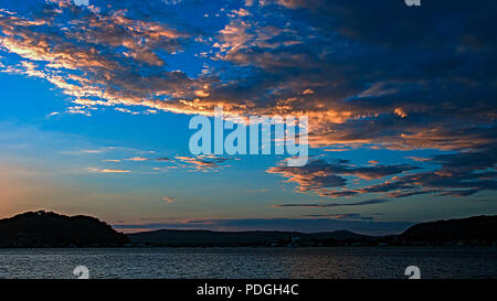 Picturesque non urban coastal orange cloud, cobalt blue sky, sunset landscape. With mostly stratocumulus clouds over water and a seashore horizon. - Stock Image