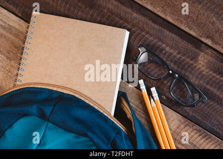 school bag, notebook,pencil,pen and eyeglasses on a wooden table.concept of school equipment and education - Stock Image