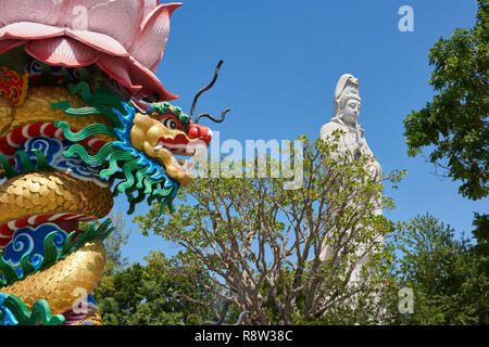 Very large statue of Buddhist goddess of mercy Guanyin in the background, in Kuang Im Chapel, near River Kwai, in Kanchanaburi, Thailand, with colourf - Stock Image