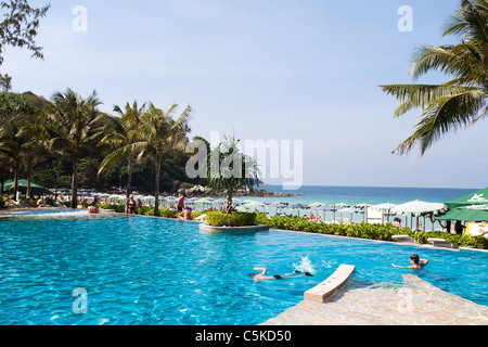 Tropical Hotel swimming pool with swimming children and view towards blue Andaman Sea - Stock Image