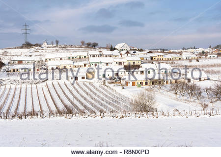 The distinctive terraced arrangement of wine cellars of Mittelberg Kellergasse during a winter snow - Stock Image