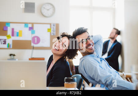 Group of young, cheerful, male and female businesspeople working together in a modern office. - Stock Image