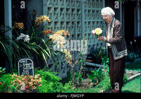 95 year old Grandmother in her rose garden at Leisure World in California with symbolic words on sign - Stock Image