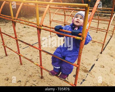little child climbing on ladder at playground - Stock Image