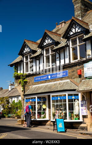 UK, Cumbria, Hawkshead, The Square, customers outside Beatrix Potter, Peter Rabbit and Friends merchandise shop - Stock Image