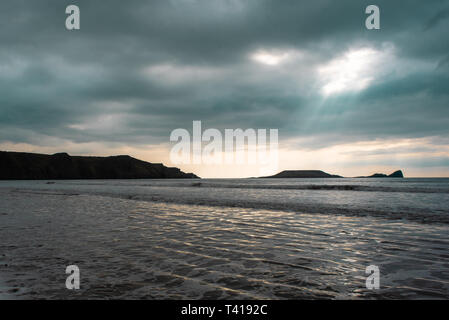 Rain clouds over Worms Head and Rhossili Bay, Wales, United Kingdom - Stock Image