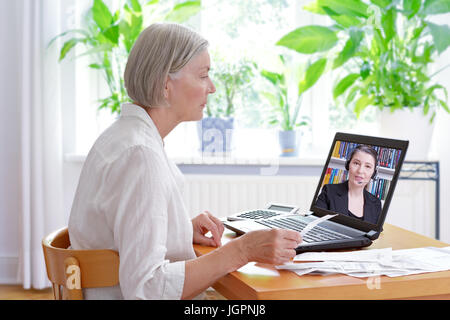 Senior woman at home with her laptop and lots of receipts, listening to an accountant before making her annual tax - Stock Image