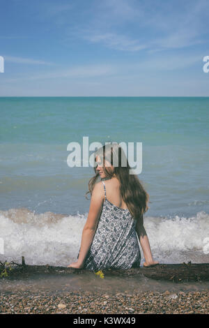 a girl sitting on a log at a lake - Stock Image