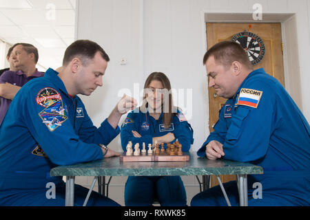 International Space Station Expedition 59 crew members Nick Hague of NASA (left), Christina Koch of NASA (center) and Alexey Ovchinin of Roscosmos (right) take a moment from pre-launch training for a game of chess at the Baikonur Cosmodrome March 7, 2019 in Baikonur, Kazakhstan. Expedition 59 crew: Christina Koch of NASA, Alexey Ovchinin of Roscosmos, and Nick Hague of NASA will launch March 14th onboard the Soyuz MS-12 spacecraft for a six-and-a-half month mission on the International Space Station. - Stock Image