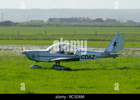 AEROTECHNIK EV-97 EUROSTAR G-CDAZ amateur built microlight landing at Leysdown on a wet grass runway. Owned and built by Michael Ludlow - Stock Image