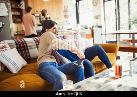 Playful woman playing video game on living room sofa - Stock Image
