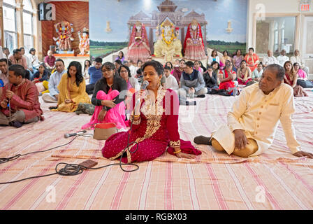 With her husband beside her, a Hindu woman sings a prayer at a congregation in Queens, New York City. - Stock Image